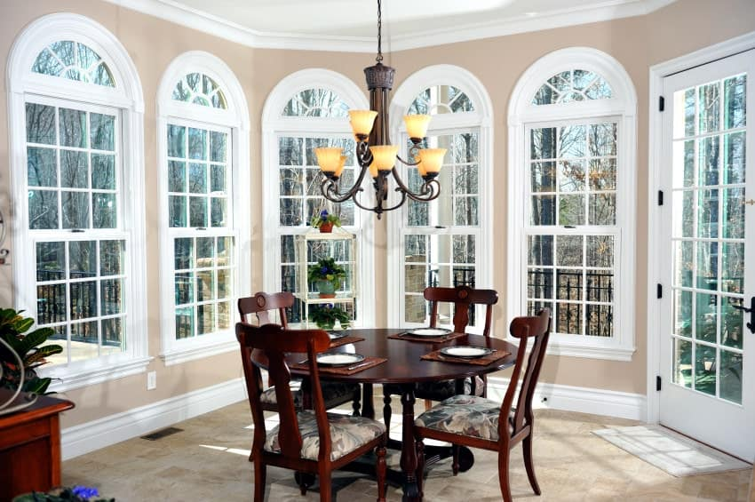 Beige dining room surrounded with arched windows and white framed door that leads out to the porch. It has floral cushioned chairs and a dark wood dining table lighted by a vintage chandelier.