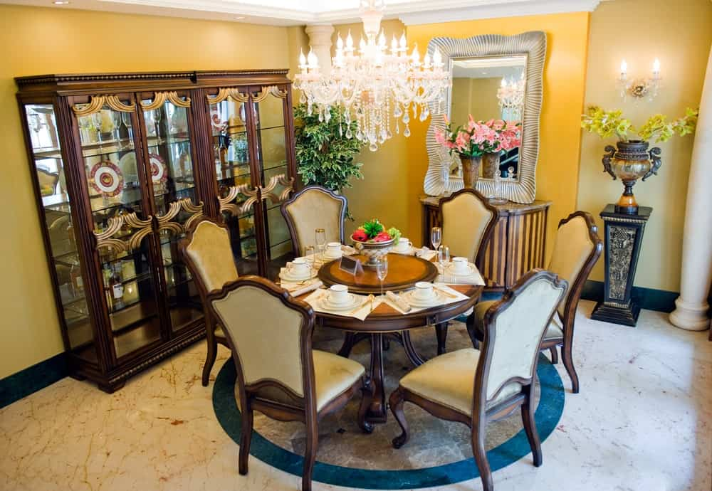 Yellow dining room features velvet cushioned chairs and a round dining table lighted by a crystal chandelier. It is accompanied by a display cabinet, flower pedestal and a striped console table paired with a gorgeous mirror.