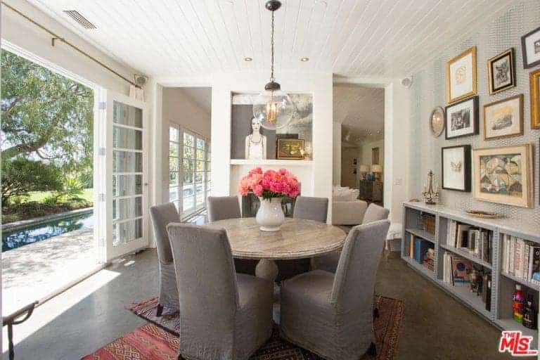 An airy dining room features gray skirted chairs and a wooden dining table lighted by a glass globe pendant that hung from the shiplap ceiling. It includes layered rugs and gallery frames mounted above the bookshelf.