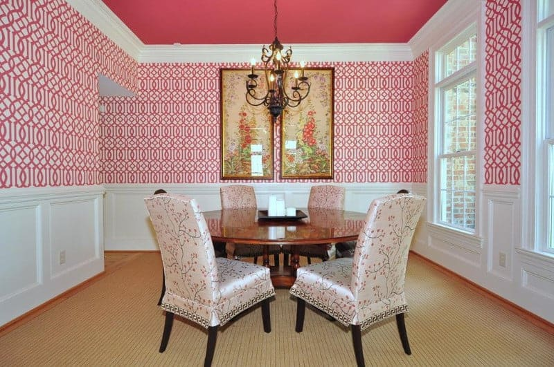 Clad in red patterned wallpaper and white wainscoting, this dining room boasts floral skirted chairs and a round dining table lighted by an ornate chandelier that hung from the red ceiling.