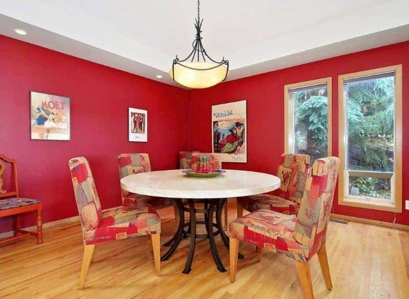 Red dining room furnished with patterned chairs and a round dining table lighted by a glass dome pendant. It has hardwood flooring and glass paneled windows framing the outdoor greenery.