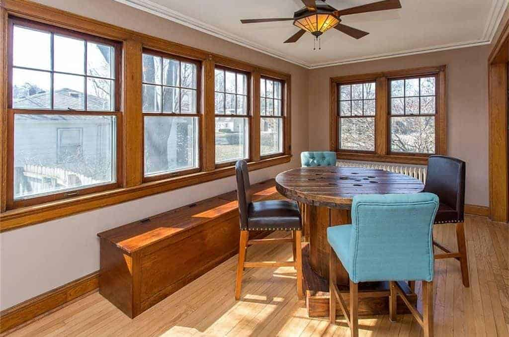 Cozy dining room illuminated by a warm flush light integrated to a ceiling fan along with natural light from the wooden framed windows complementing with the bench. It has a rustic dining table paired with black leather and blue tufted chairs.