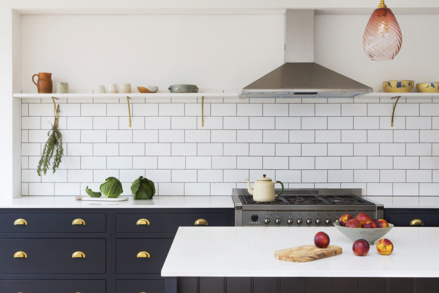 Pared down in-frame hardwood shaker kitchen with unlacquered brass handles.