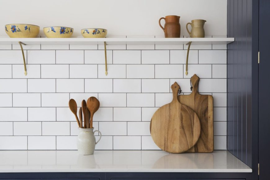 Floating shelf with brass joints and white tile backsplash.