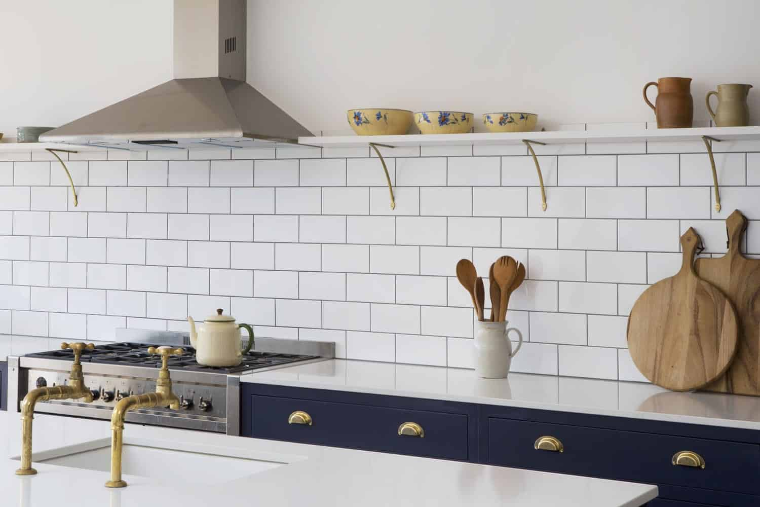 Floating shelving with white kitchen tile backsplash and brass accents.