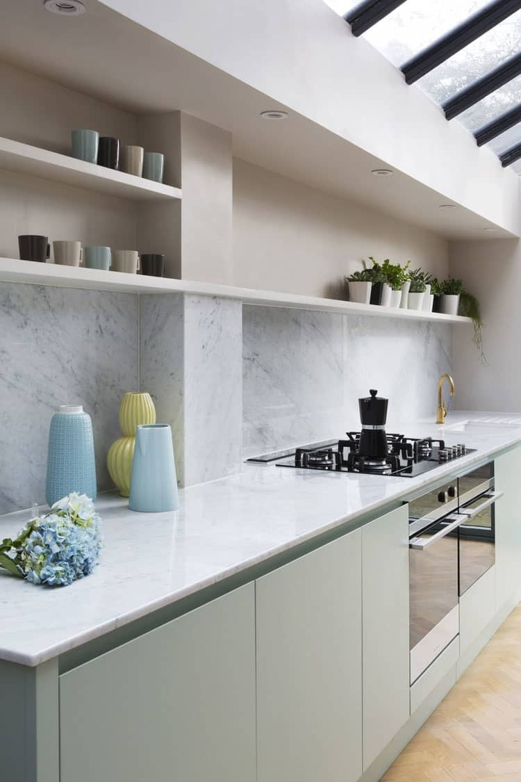 Bespoke kitchen design with marble worktop and brass top sink faucet.