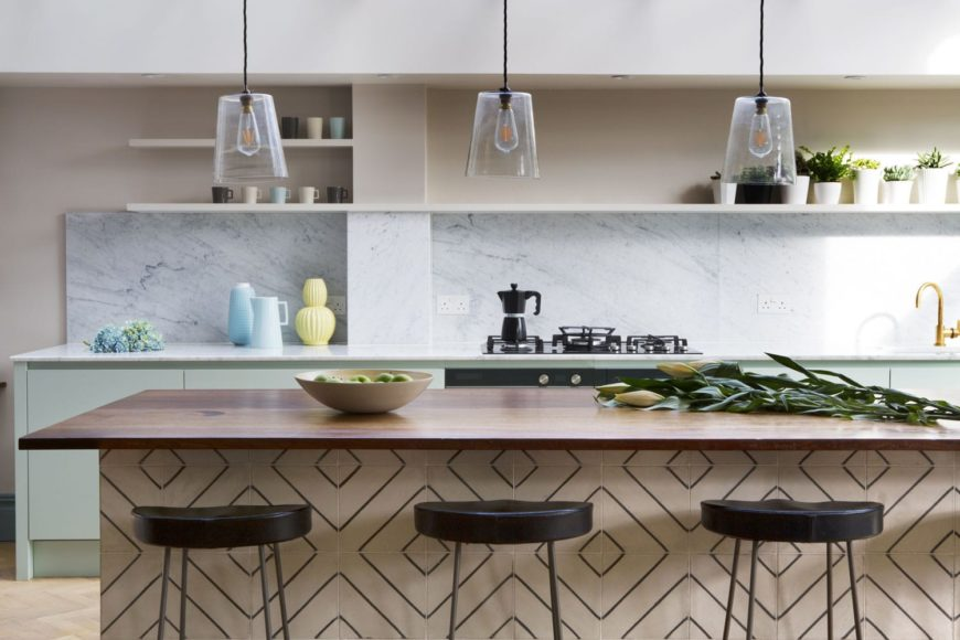 Pendant lighting above the kitchen island with reclaimed wood worktop and reclaimed tiles.