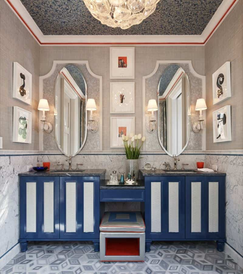 Eclectic powder room decorated with white framed wall arts and oval shaped mirrors mounted above the blue sink vanities accompanied by a gray cushioned stool.