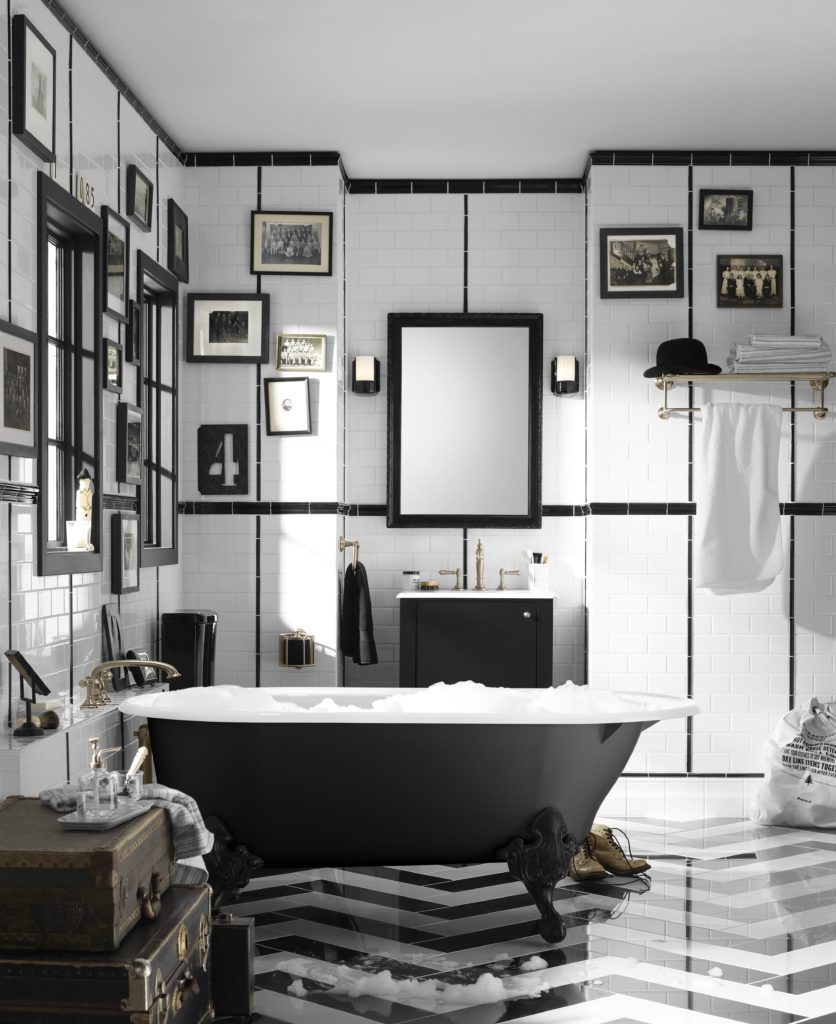 Eclectic bathroom with chevron tiled flooring and white brick walls filled with framed photos and mirrors. It includes a black matte sink vanity and clawfoot tub paired with chest side table.