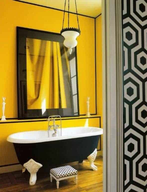 Yellow bathroom offers a large mirror flanked by mini sculptures along with a dotted stool and black clawfoot tub lighted by a white glass pendant.