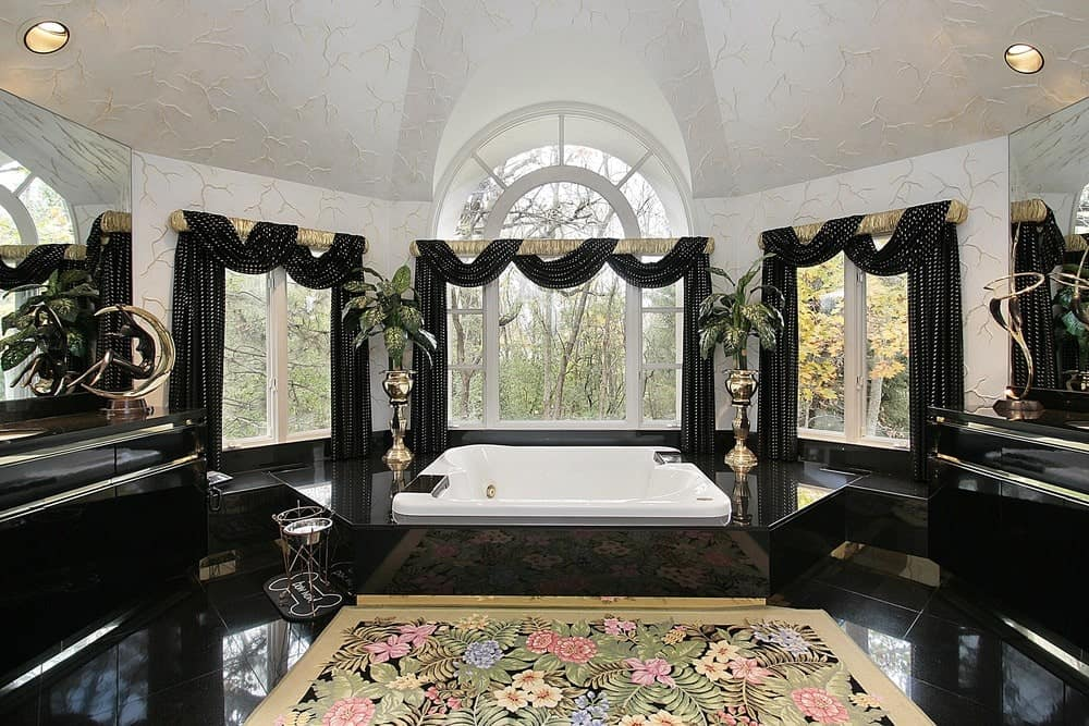 Classy bathroom features a deep soaking tub beneath the glazed windows dressed in elegant valances. It has white textured ceiling extending to the walls and a black tiled flooring topped with a charming floral rug.
