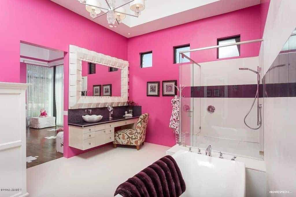 A lovely floral chair sits at a floating sink vanity in this pink bathroom with a freestanding tub and walk-in shower enclosed in glass. It is illuminated by a white chandelier that hung from the tray ceiling.