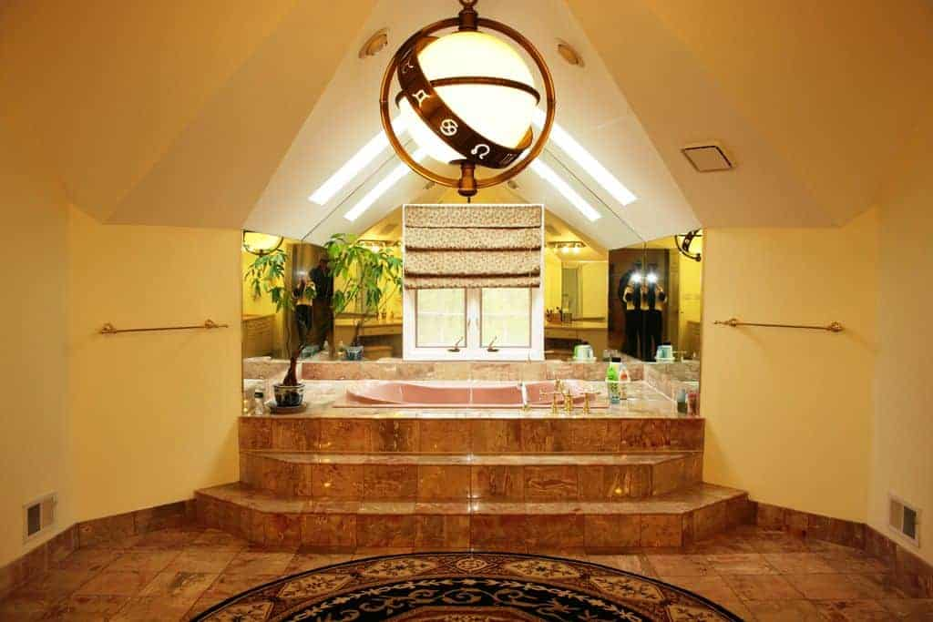 Large Eclectic-style bathroom with steps toward the drop-in tub under a pitched ceiling with skylights.