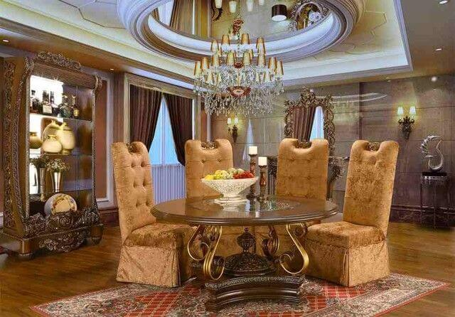 A glamorous eclectic dining room with a gorgeous chandelier set on a stunning ceiling. It has elegant round dining table paired with luxurious seats. The shelving adds elegance to the room as well.
