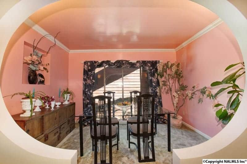 Eclectic-style dining room with pink walls and ceiling. There's a square glass top dining table with four modern seats. There are potted indoor plants on two corners of the room as well.
