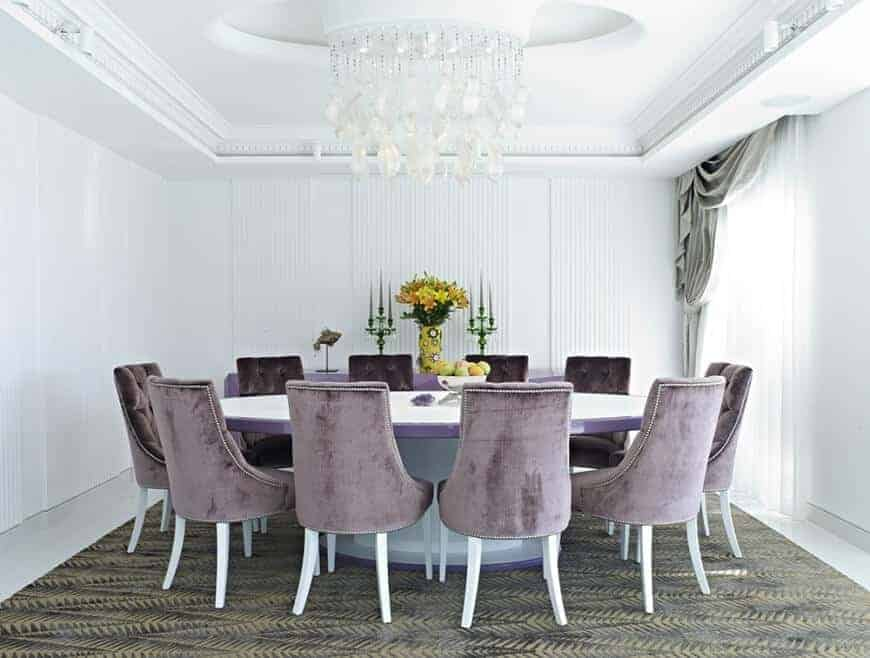 Large dining kitchen boasting a large round table with classy purple chairs lighted by a glamorous white chandelier hanging on a beautiful ceiling. The room has white walls and elegant window curtains.