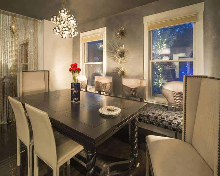 An eclectic dining room featuring a square dining table set lighted by a charming pendant light. The room is surrounded by gray walls and ceiling.