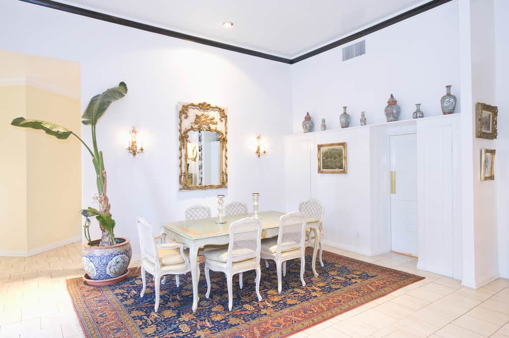 A bright dining area with its white walls and ceiling. It has a classy-looking dining table set along with a large potted indoor plant on the side.