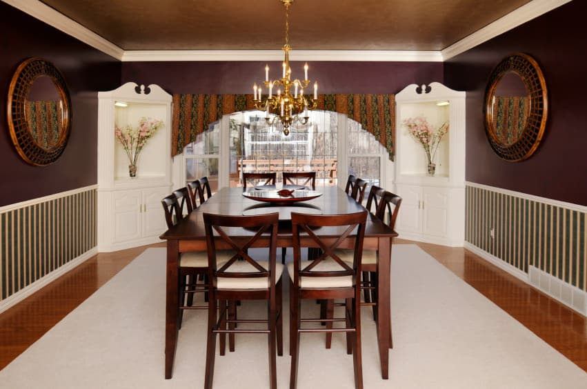 Eclectic dining room with purple walls and a brown ceiling. The room has a wooden dining table and chairs set lighted by a gorgeous chandelier.