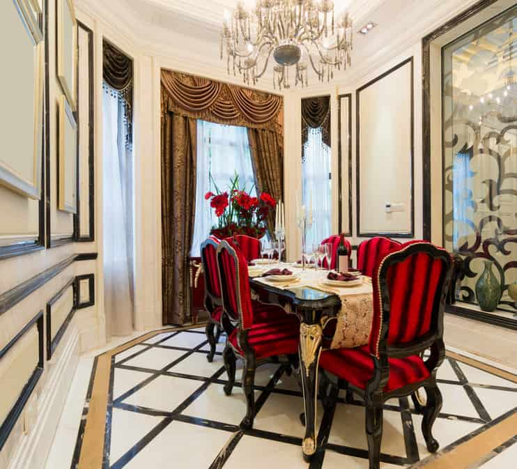 Eclectic dining room with stylish flooring and classy decorated walls with attractive wall decors. The room is lighted by a glamorous chandelier hanging from the high ceiling.