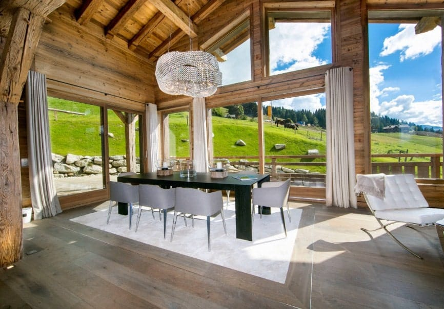 Large dining room featuring wooden walls and a wooden ceiling with exposed beams. The glass windows overlook the relaxing and peaceful grassland farm view.