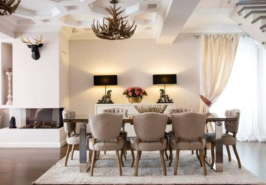 A luxurious dining room boasting a dining table set with a classy set of seats. The area has a very stunning ceiling lighted by enchanting ceiling lights.