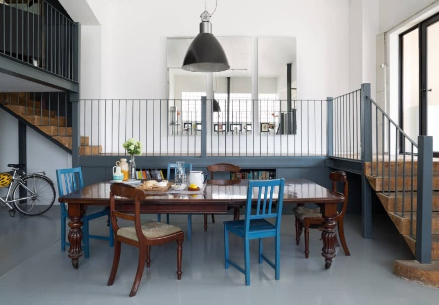 Eclectic dining room featuring a classy wooden rectangular dining table set situated on the home's gray flooring. The table set is lighted by a pendant light.