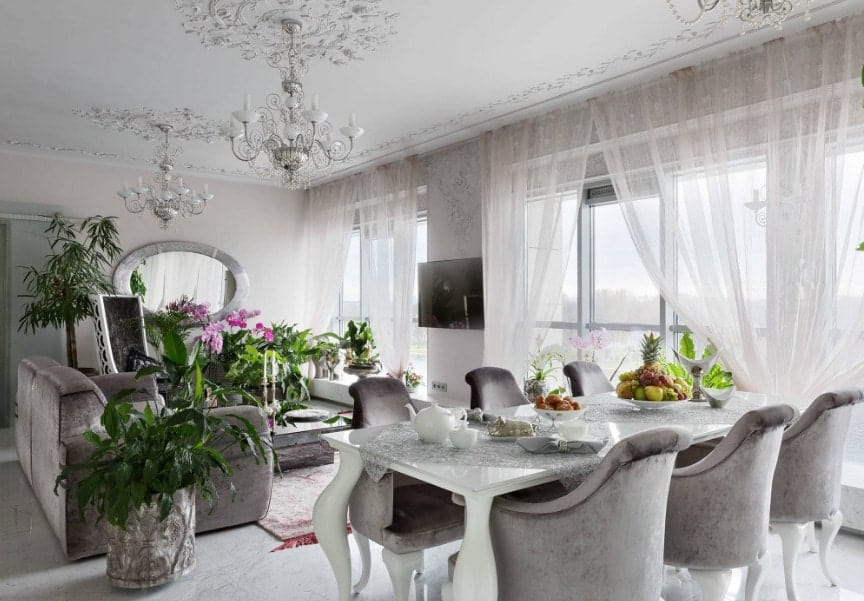 A great room with a silver and gray color scheme that looks elegant. The room has a cozy living space with a large gray couch and a dining area featuring a dining table set with gray seats. The area is lighted by beautiful chandeliers.