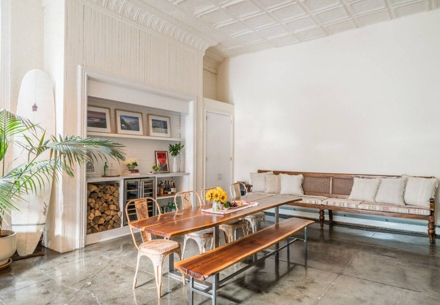 A spacious dining room featuring a wooden dining table with a wooden bench. There's a bench seating with a pair of foam on the side. The room is surrounded by white walls and a white tall ceiling.