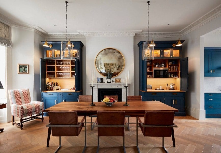 A dining room featuring stylish hardwood flooring and two cabinetry with counters. There's a fireplace on the side. The wooden dining table and chairs set is lighted by classy pendant lights.