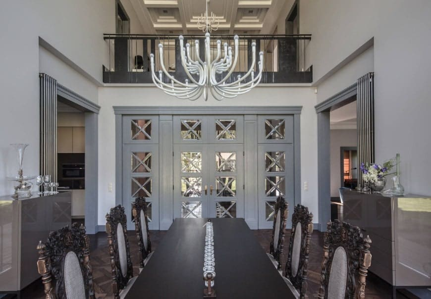 This eclectic dining room has a gorgeous dining table and chairs set lighted by an eye-catching chandelier hanging from the two-storey ceiling.