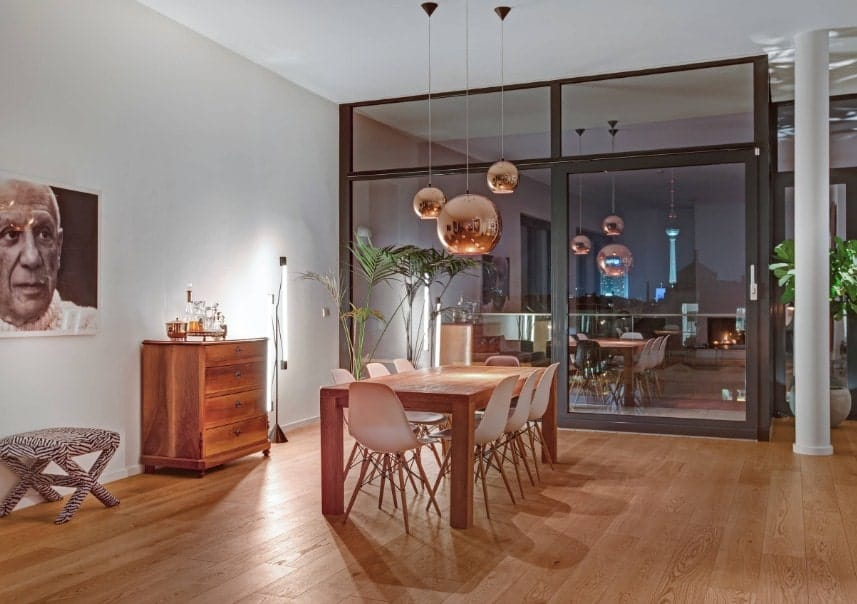 Large dining room area featuring a wooden dining table set lighted by charming pendant lights and is set on the home's hardwood flooring.