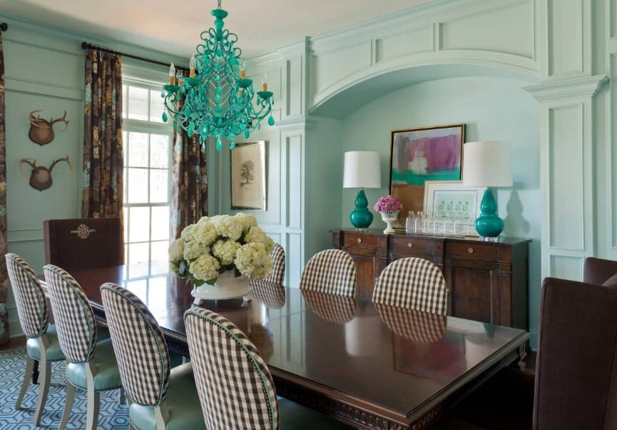 This eclectic dining room features a classy dining table set lighted by a turquoise-finished chandelier. The room is enveloped by the green walls.