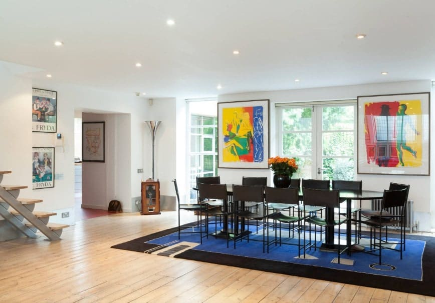 A spacious eclectic dining room featuring an oval dining table set on top of a stylish area rug covering the hardwood flooring. The colorful wall decors near the windows are also attractive.