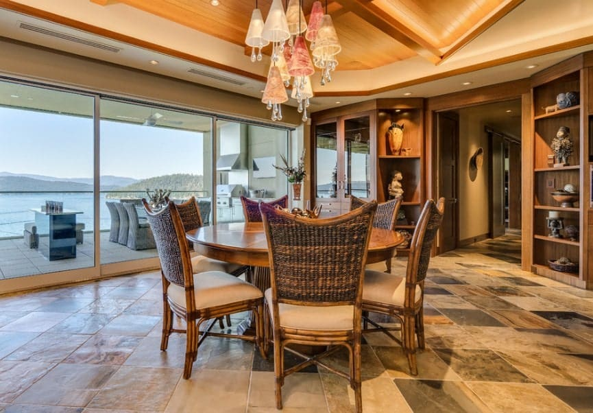 Large eclectic dining room with an elegant round dining table set lighted by glamorous ceiling lights hanging from the stunning ceiling. The tiles flooring looks classy while the built-in shelving along with the decors are absolutely attractive.