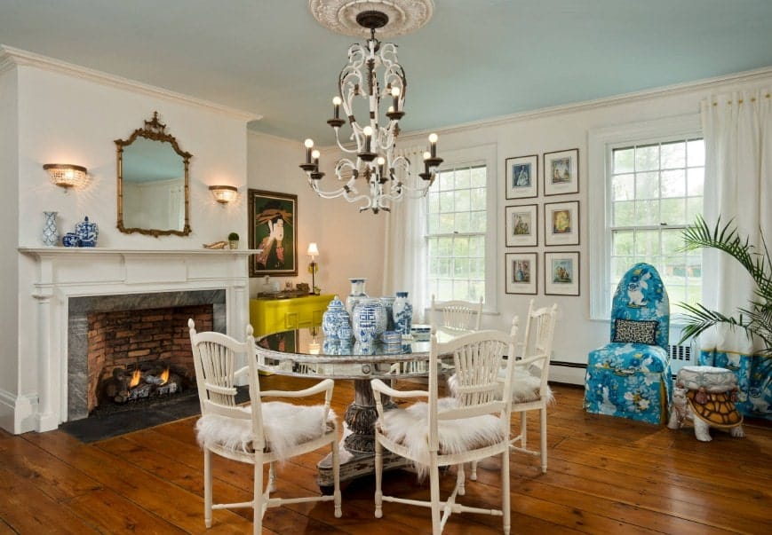 A spacious dining room featuring a round table with lovely seats, lighted by a gorgeous chandelier. The room also features a fireplace.