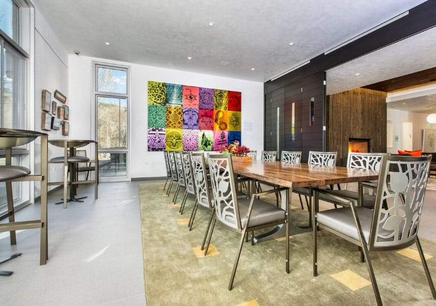 Large dining room featuring a long dining table set on a large area rug. The room is surrounded by white walls with lots of wall decors.