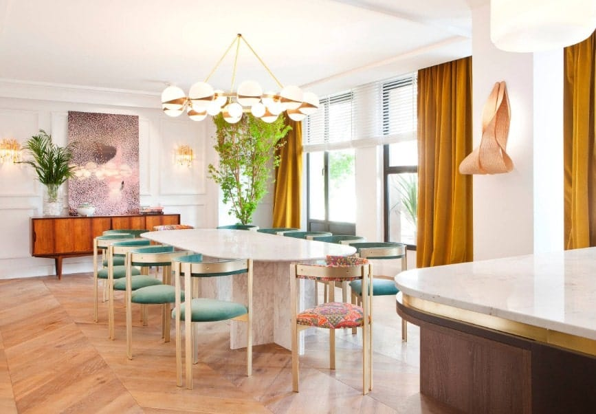 Large eclectic dining room with stylish hardwood flooring, white walls and a white ceiling. The dining table set with modish chairs are lighted by a fancy ceiling light.