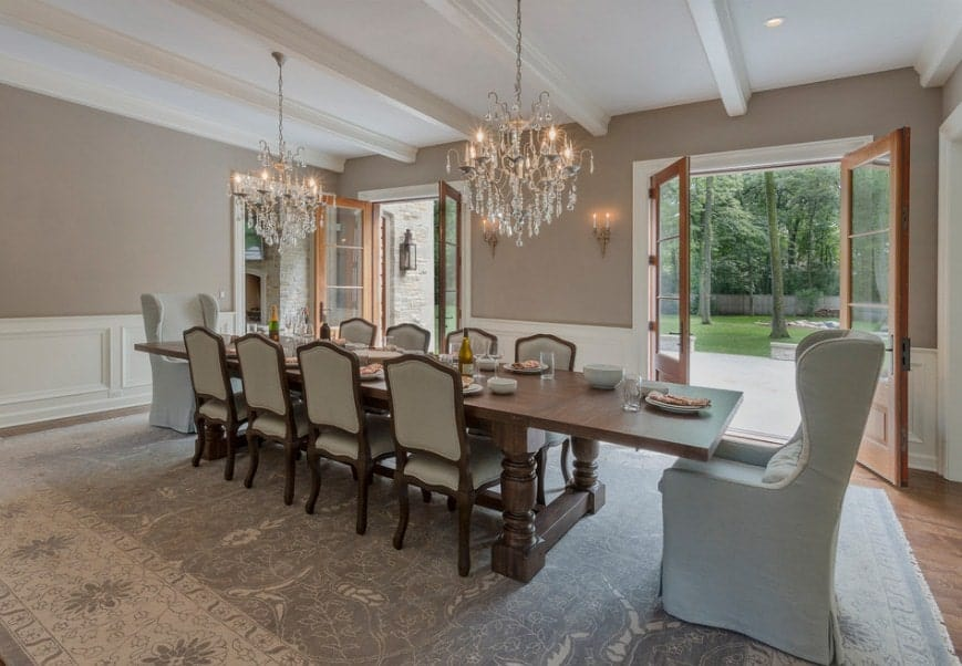 A large and elegant eclectic dining room with a classy dining able set for 10 lighted by fancy chandeliers. The large area rug adds elegance to the room.