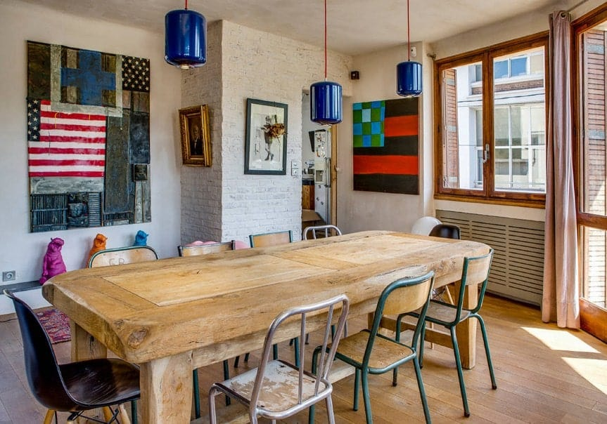 Eclectic dining room with a wooden dining table set lighted by blue pendant lights. There are many wall decors on the home's walls.