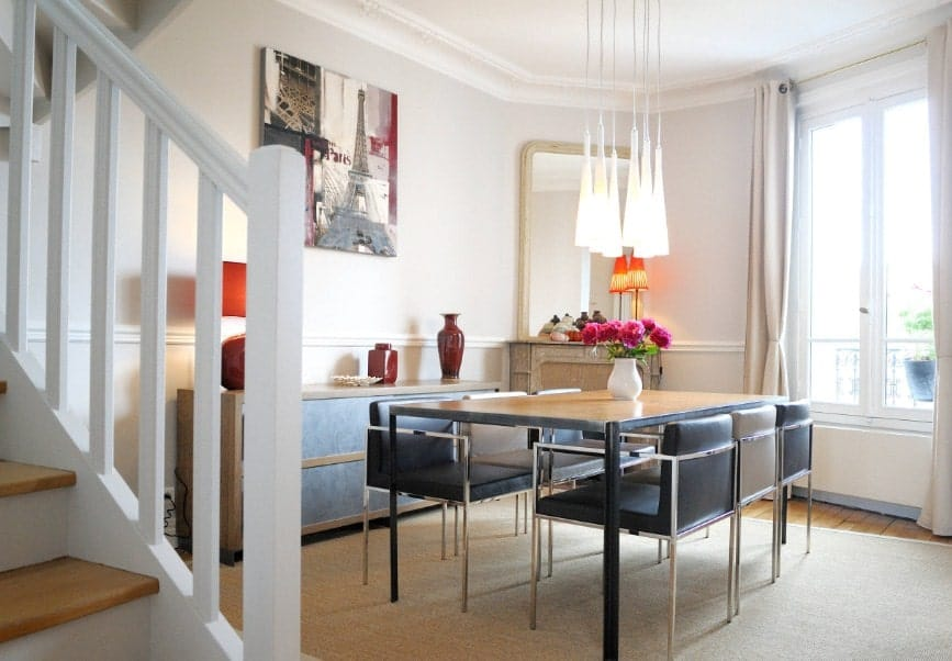A simple-looking eclectic dining room with a dining table set paired with modish chairs and is lighted by charming pendant lights.
