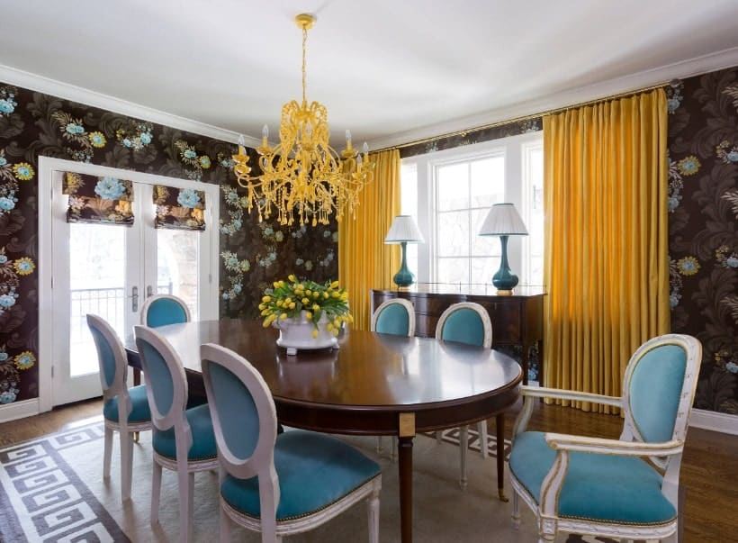 Eclectic dining room with a beautiful wall design and a pair of yellow window curtains matching the yellow chandelier just above the oval dining table set.