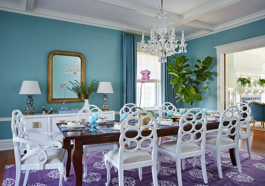 Large eclectic dining room with elegant blue walls and white ceiling. The dining table and chairs are set on top of a classy purple rug and is lighted by a fancy chandelier.