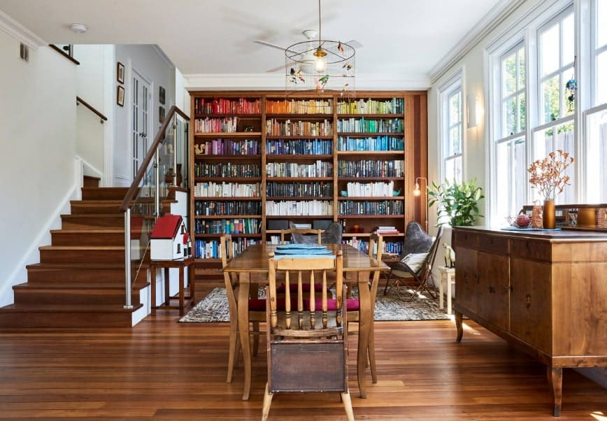 A dining area and library space featuring a wooden rectangular dining table set along with large built-in shelving housing hundreds of books. The area is lighted by a fancy ceiling light.
