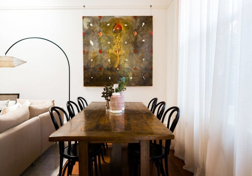 A focused shot at this small eclectic dining space with a rectangular dining table set along with a very attractive wall decor.