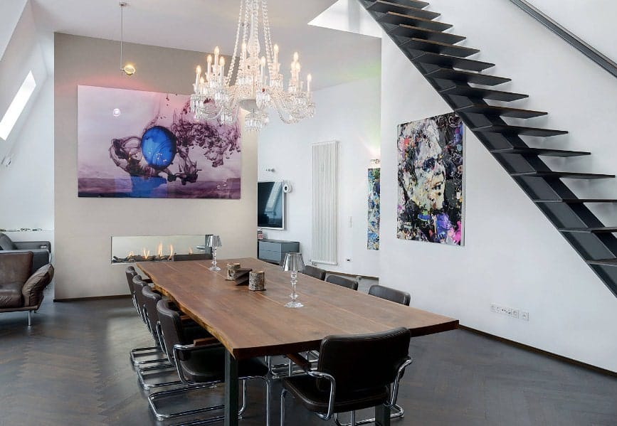 A spacious dining area featuring a wooden dining table set paired with modern seats and is lighted by a glamorous chandelier. There's a gas fireplace on the side. The walls feature artistic wall decors.