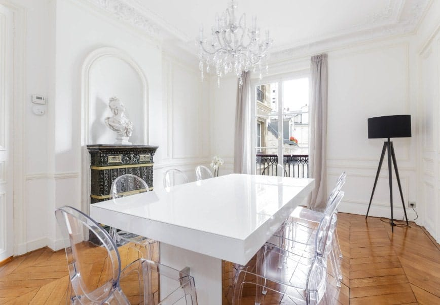 Eclectic dining room featuring herringbone-style hardwood flooring and white walls matching the white dining table set paired with transparent seats. The table set is lighted by a lovely chandelier.