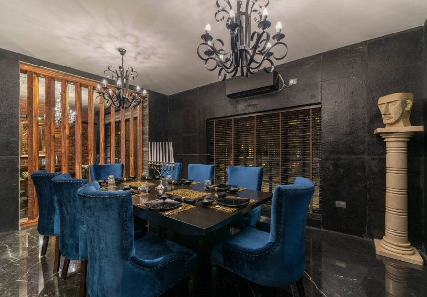 Eclectic dining room with elegant black flooring and walls. The black dining table set is paired with elegant blue seats lighted by a pair of black chandeliers.