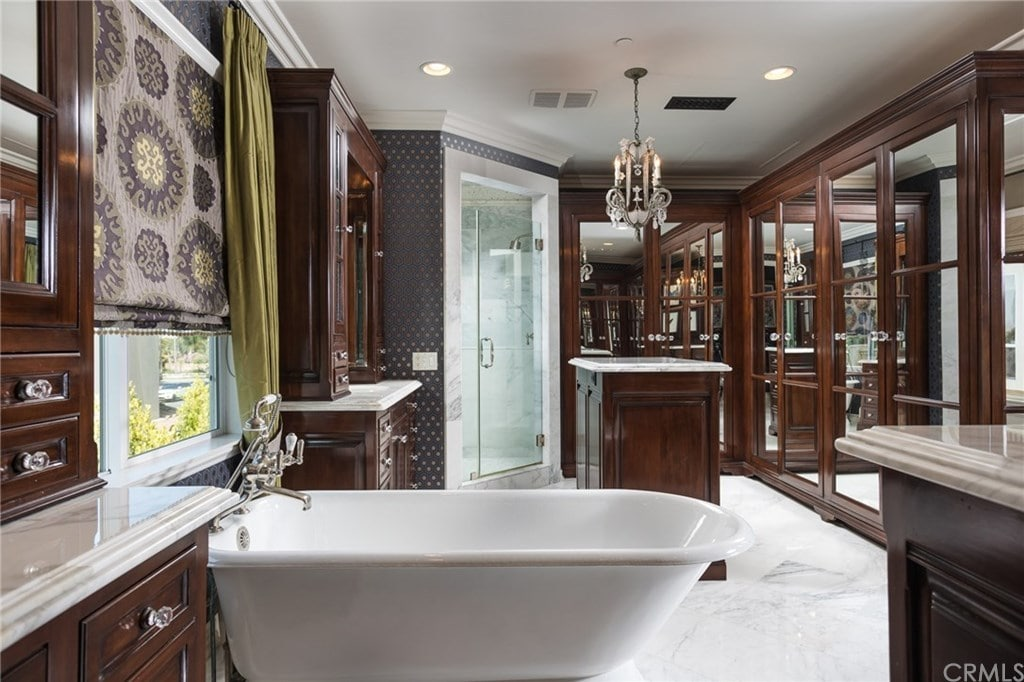Luxury primary bathroom with a walk-in shower and a freestanding tub flanked by dark wood vanities that blend in with the islands and mirrored walls. It has marble flooring and a glazed window dressed in a floral roman shade and green draperies.