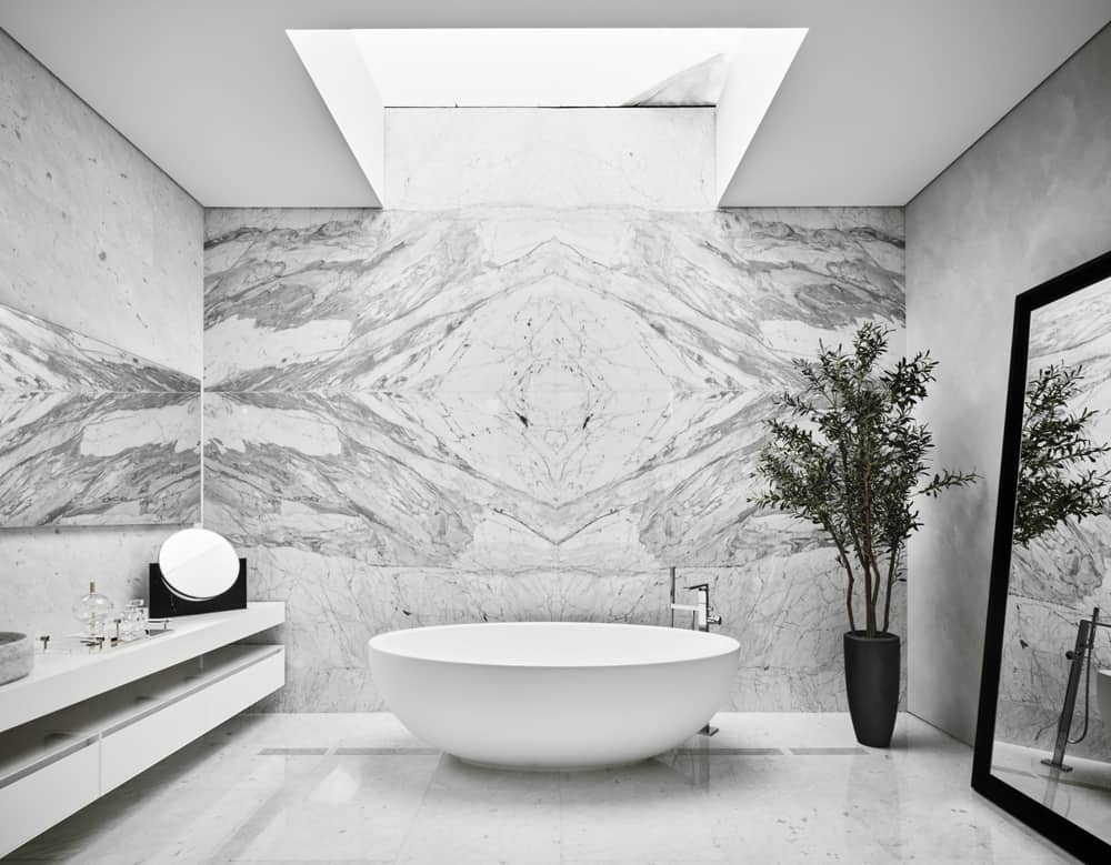 This is a view of the primary bathroom with a large white porcelain freestanding bathtub on the far side by the white marble wall topped with a skylight and adorned with a potted plant and leaning mirror.